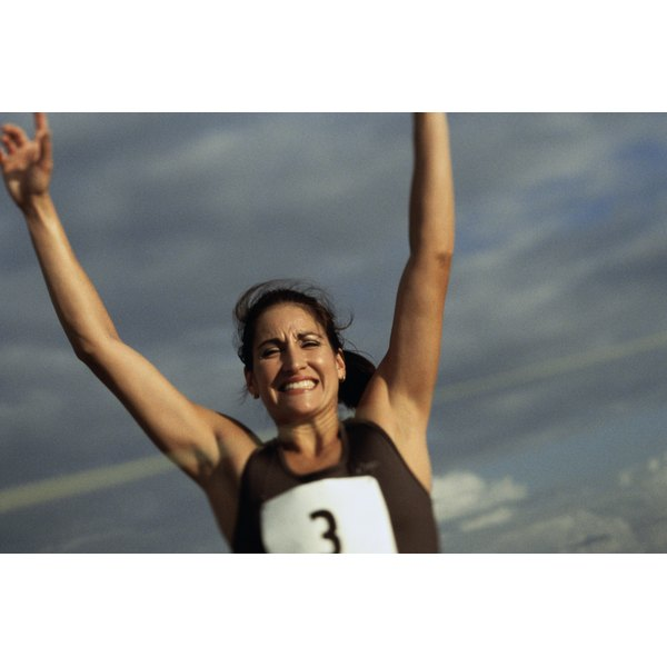 Woman raising her hands after finishing a race.