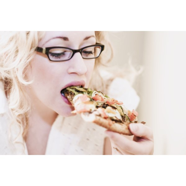 A young woman eating a slice of pizza.