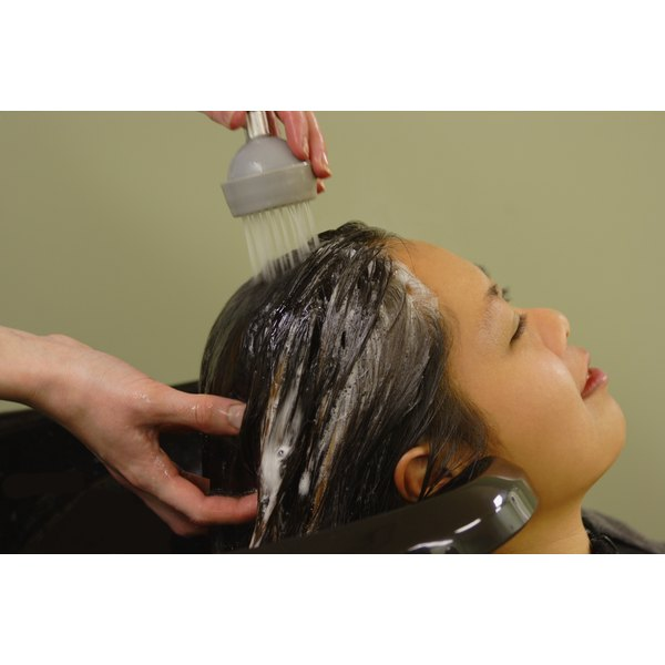A woman is getting her hair washed at the salon.