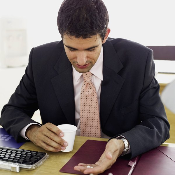 Businessman sitting at his desk with medicine and a glass of water
