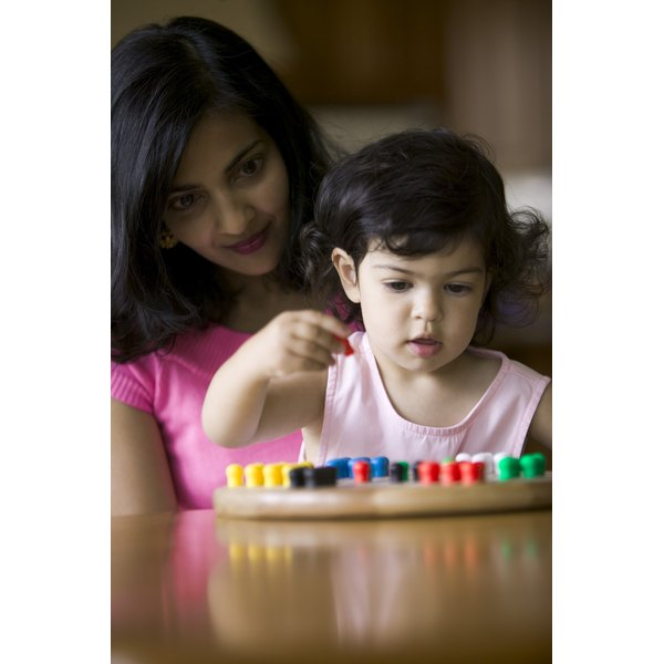 toddler sitting with mom attempting to grab a peg from development peg board