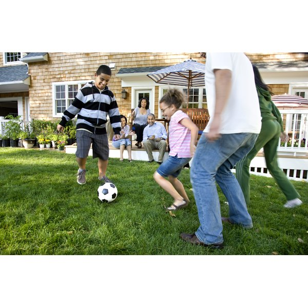 Family playing soccer in their backyard.