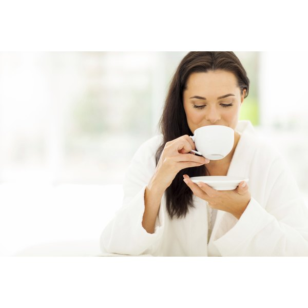 A young woman drinks a cup of coffee at home.