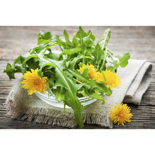 Dandelions in a bowl on a wooden table.