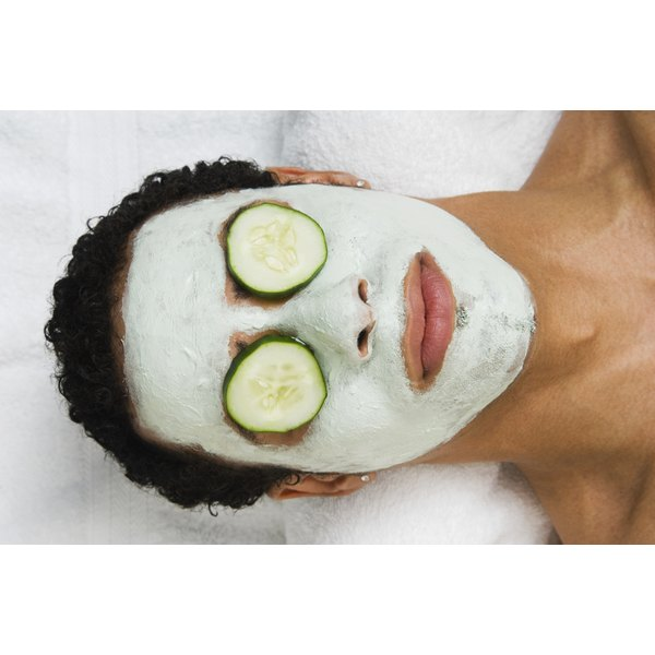 Young man wearing a face mask with cucumbers over his eyes.