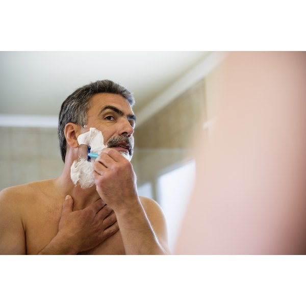Close-up of an older man shaving in a mirror.