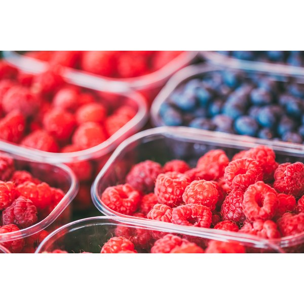 Raspberries and blueberries for sale at a market.
