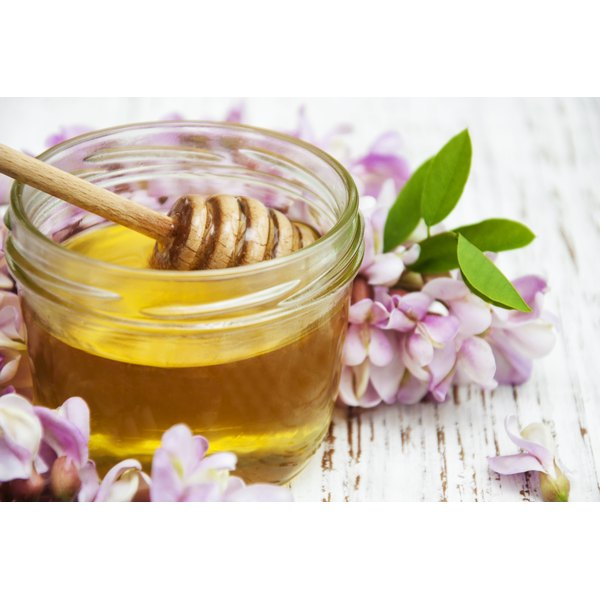 A jar of honey next to flower blossoms.