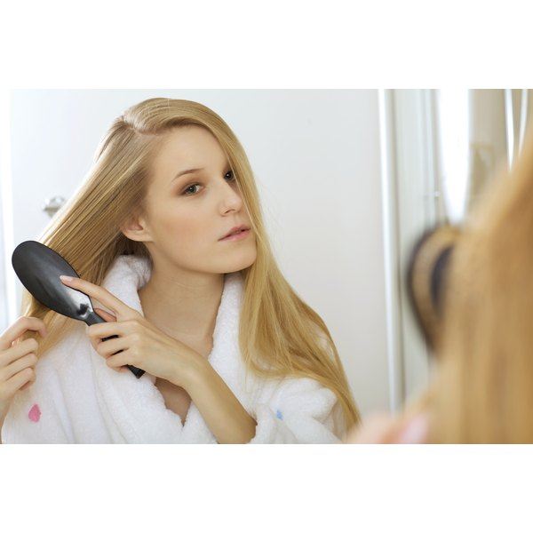 A young woman brushing her hair in the mirror.