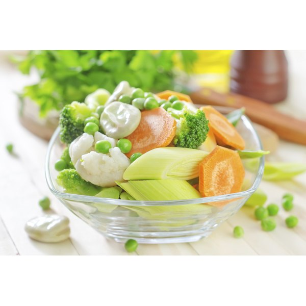 A bowl of steamed vegetables in a glass bowl on the kirtchen counter.
