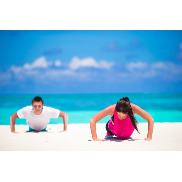 A man and woman are exercising on the beach.