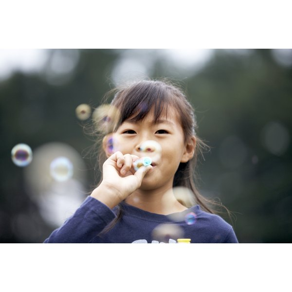 A young girl is blowing bubbles.
