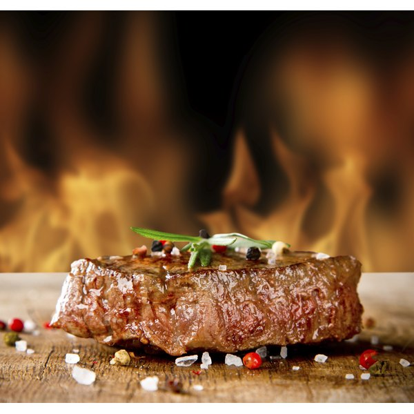 A grilled beef steak sits on a board before a background of flames.