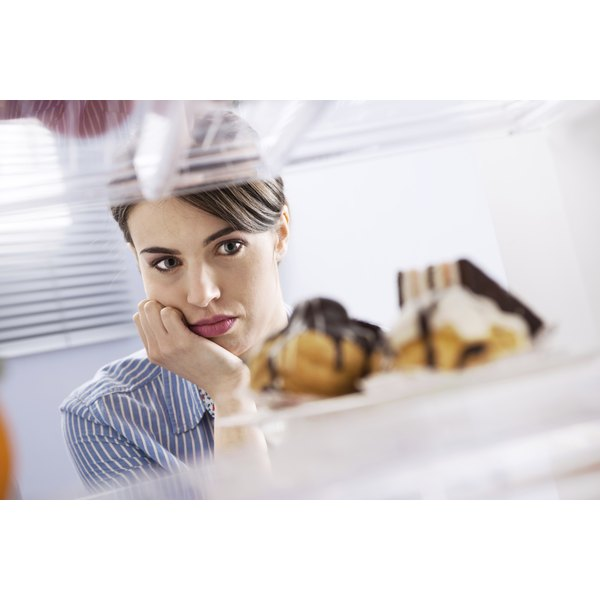 A woman is eyeing some sweets in the refrigerator.