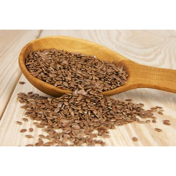 Flaxseed spilling out of a wooden spoon