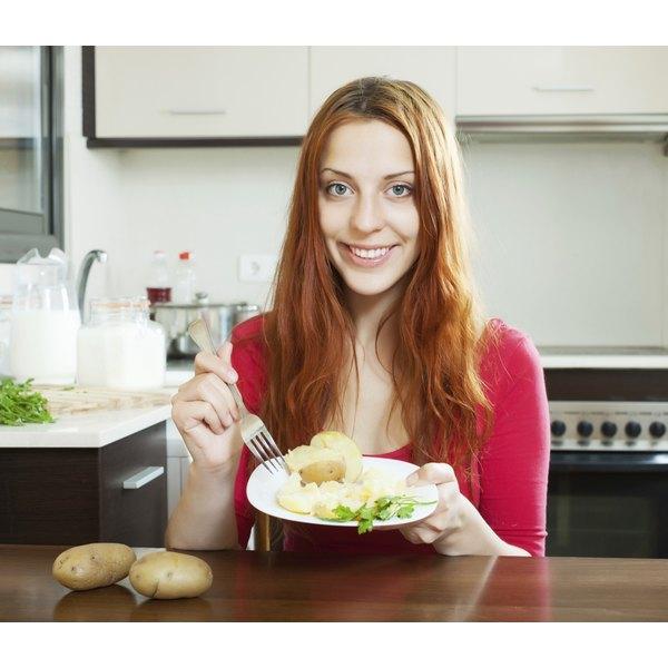 Woman eating a baked potato.