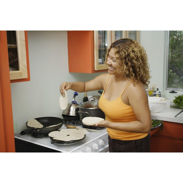 A woman is warming tortillas on the stove.