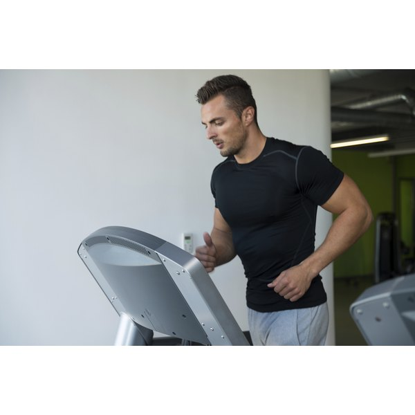A muscular man is running on a treadmill.