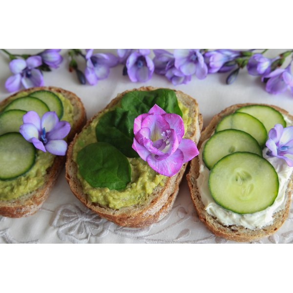 Open face sandwiches with avocado, cream cheese and cucumbers on a table with tropical flowers.
