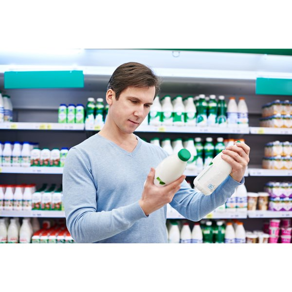 man reading the label of soy milk bottle at grocery store
