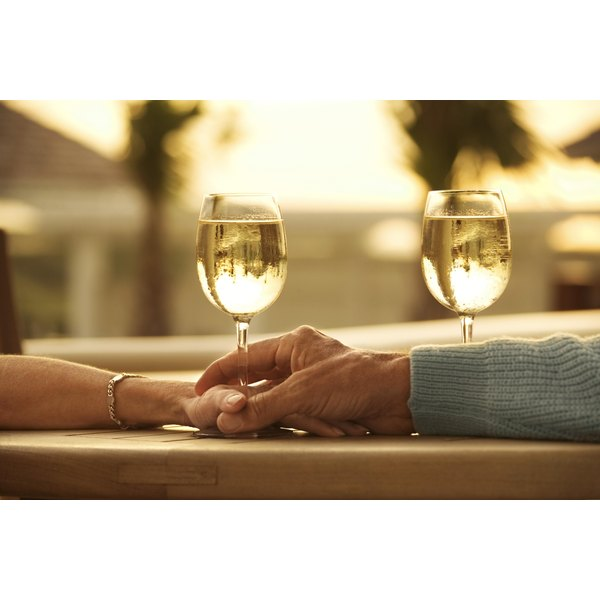 Couple holding hands at an outdoor table, next to two glasses of wine