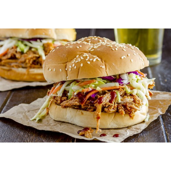A pulled pork sandwich with coleslaw and BBQ sauce.