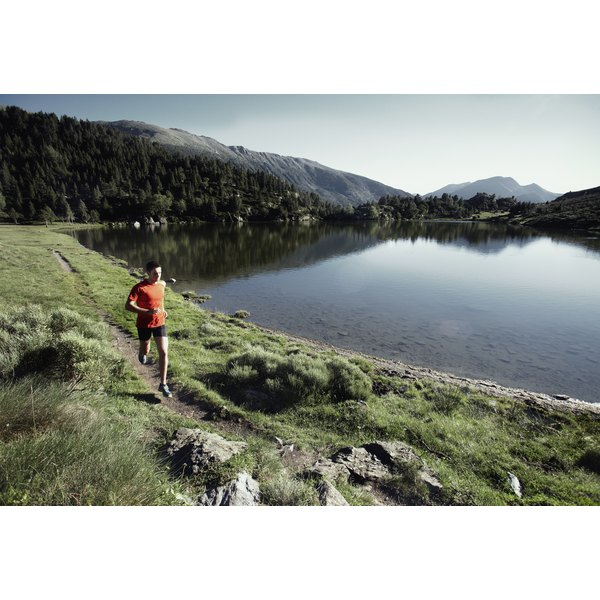 A trail runner near a lake at the base of a mountain.