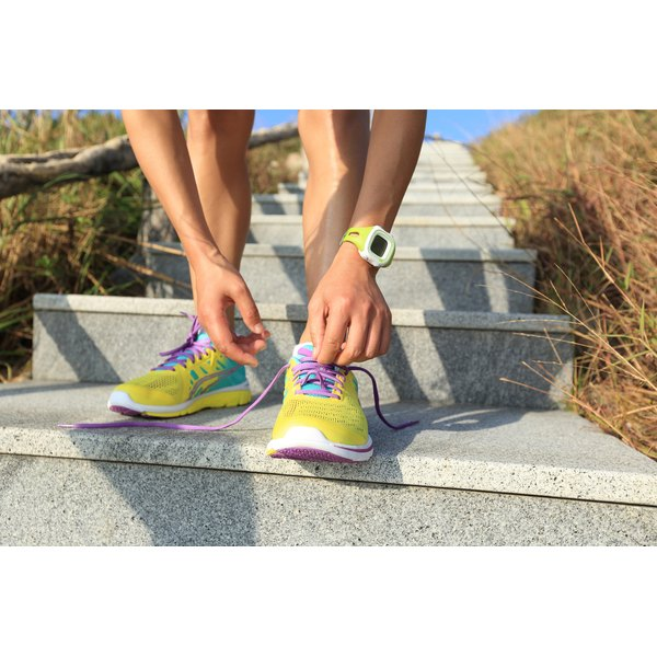 A woman is tying her running shoes.