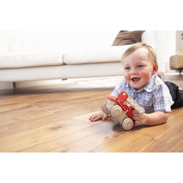 A young tot plays with a wooden toy on the living room floor.