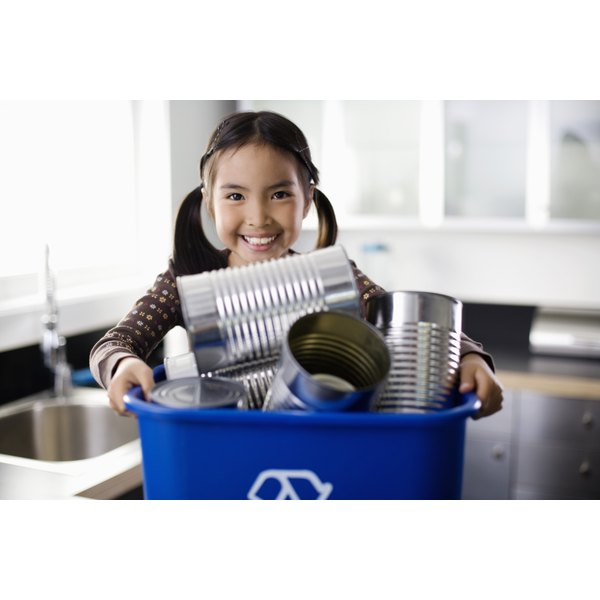 An enthusiastic girl carrying a recycling bin.