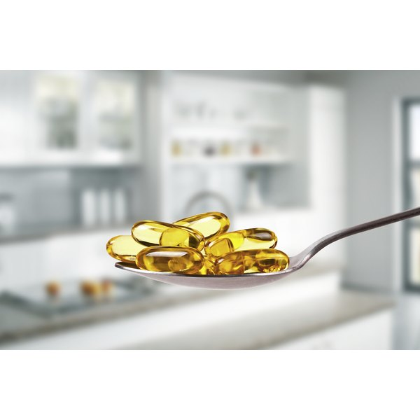 A spoon filled with fish oil capsules in front of a kitchen.