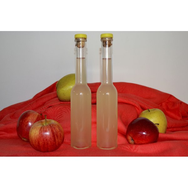Two bottles of apple cider vinegar and apples.