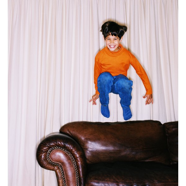 Boy jumping on leather sofa.