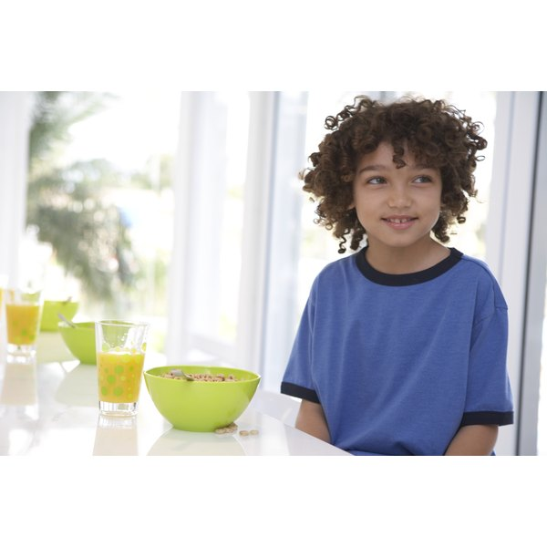 A child sitting next to a bowl of cereal at the breakfast table.