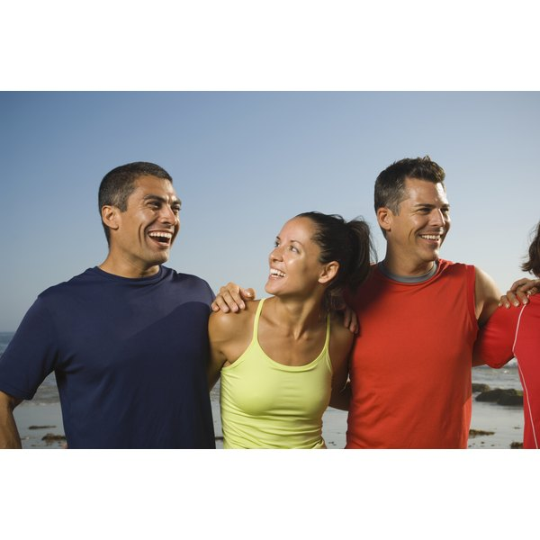 Athletic people with their arms around each other smiling.