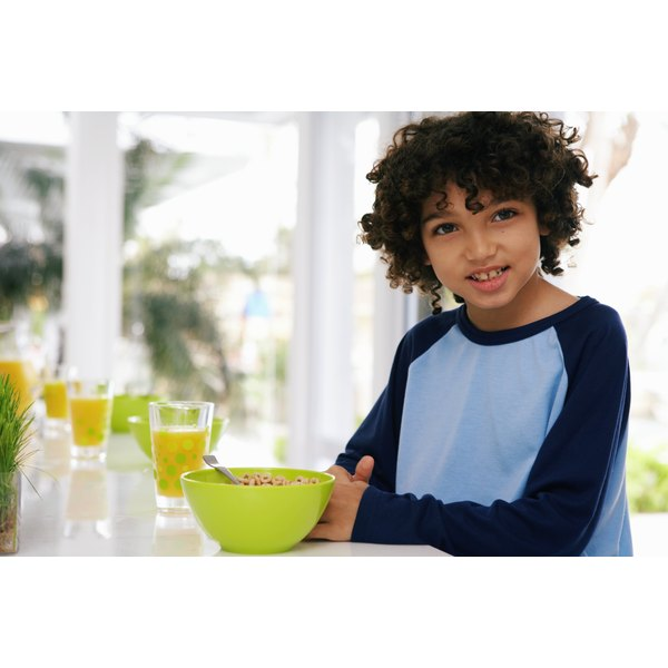 A young boy is eating a bowl of cereal.