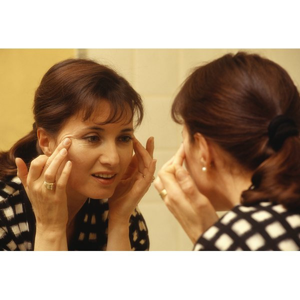 A mature woman looking in the mirror pulling on her skin.