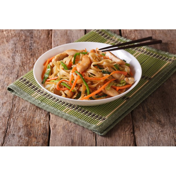 A chicken, veggie and noodle dish on a wooden table.