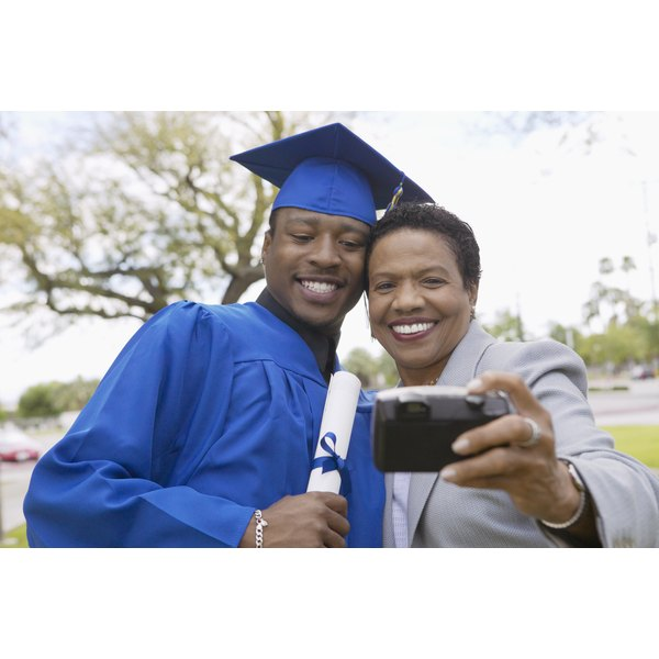 Mother taking photo with graduated son