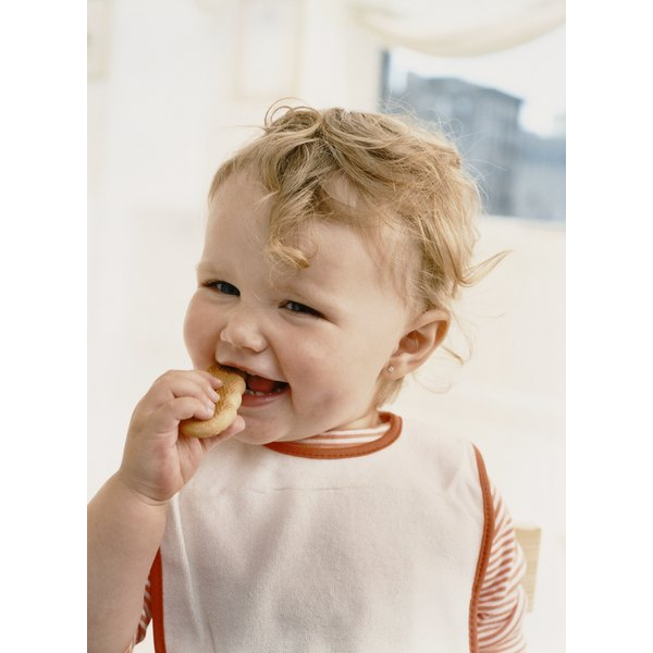baby eating with bib on - feeding himself