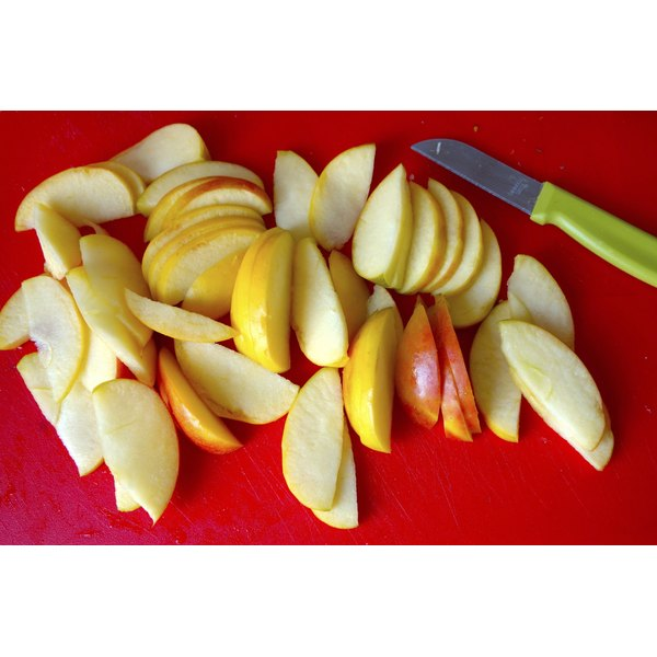 Sliced apples on a red cutting board.