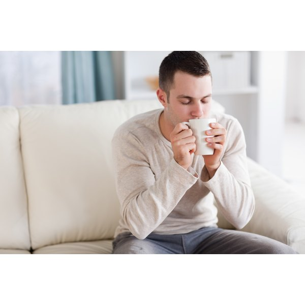 A man inhaling the steam from a mug on the sofa.