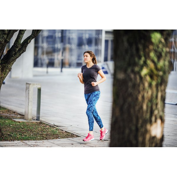 A young woman is running outside.