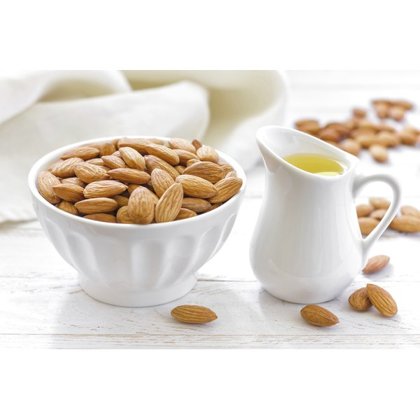 A pitcher of almond oil next to a bowl of almonds.