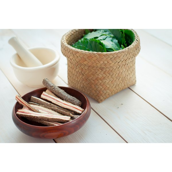 A bowl of neem bark on a table with a mortar and pestle.