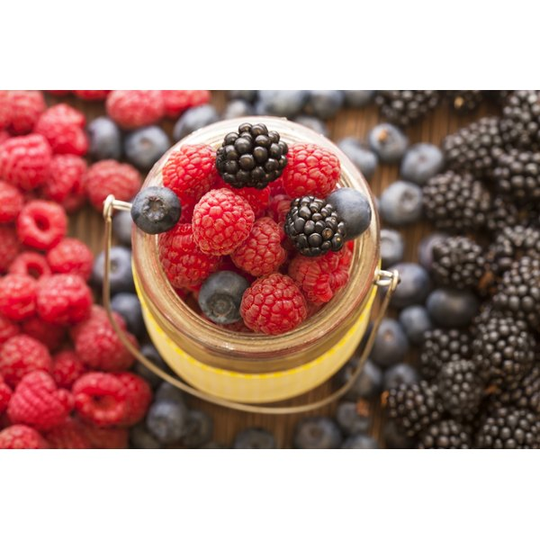 An overhead view of raspberries, blueberries and blackberries in a jar on a wooden table.