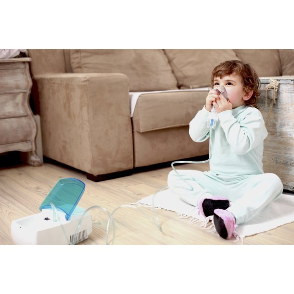 Toddler girl sitting on the ground using a nebulizer.