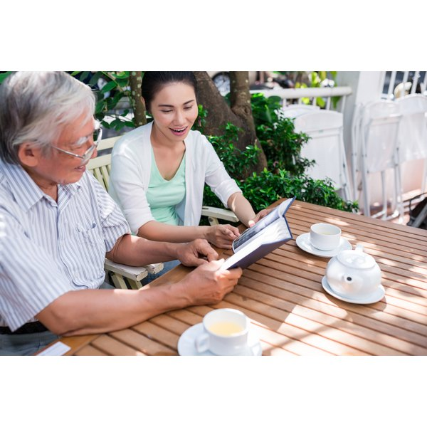 Elderly father and daughter talking at table on outside patio.