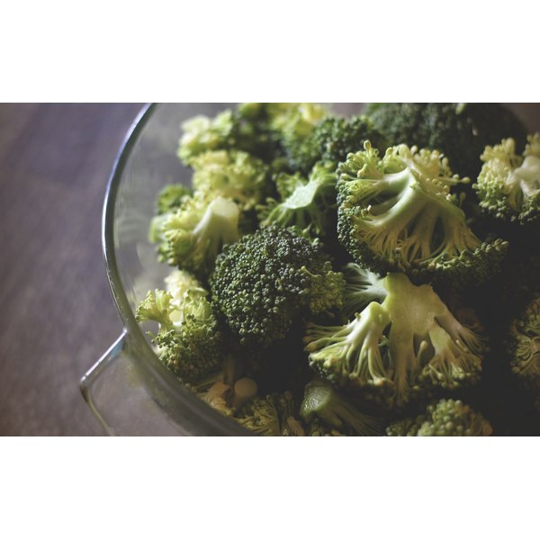 A close-up of broccoli in a glass bowl on a wooden table.