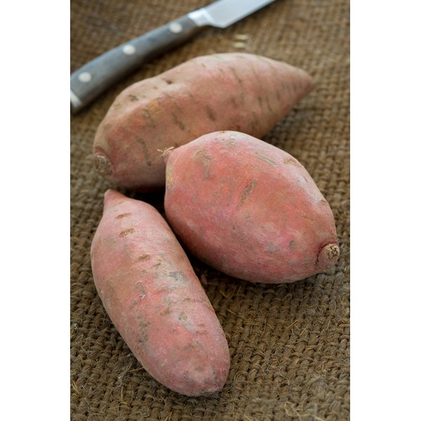 close up of sweet potato in kitchen with knife on burlap